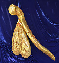Glitoris,a gold 100-to-1 scale model of the clitoris, shown on a purple cloth