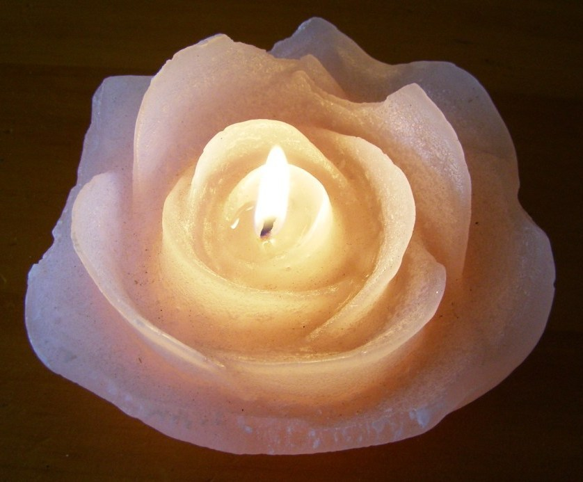 A pink rose candle that is lit