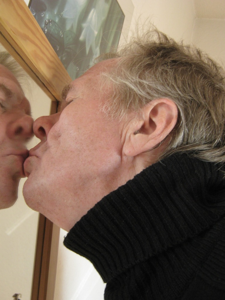 Mature man kisses himself in mirror