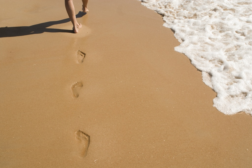 Feet leave footprints where sea and beach meet